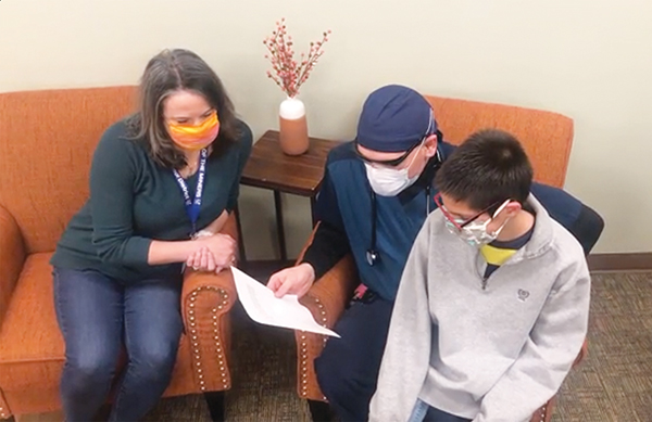 Family reading letter with face masks on